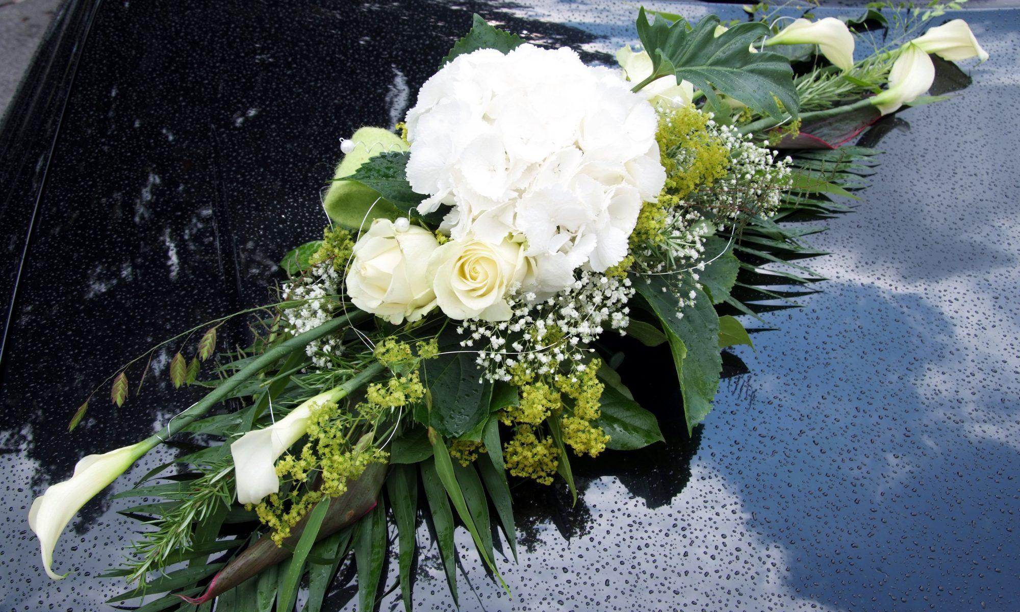 Ein Autogesteck auf einer schwarzen Motorhaube mit weißen Blumen und verschiedenen grünen Blättern länglich gesteckt.