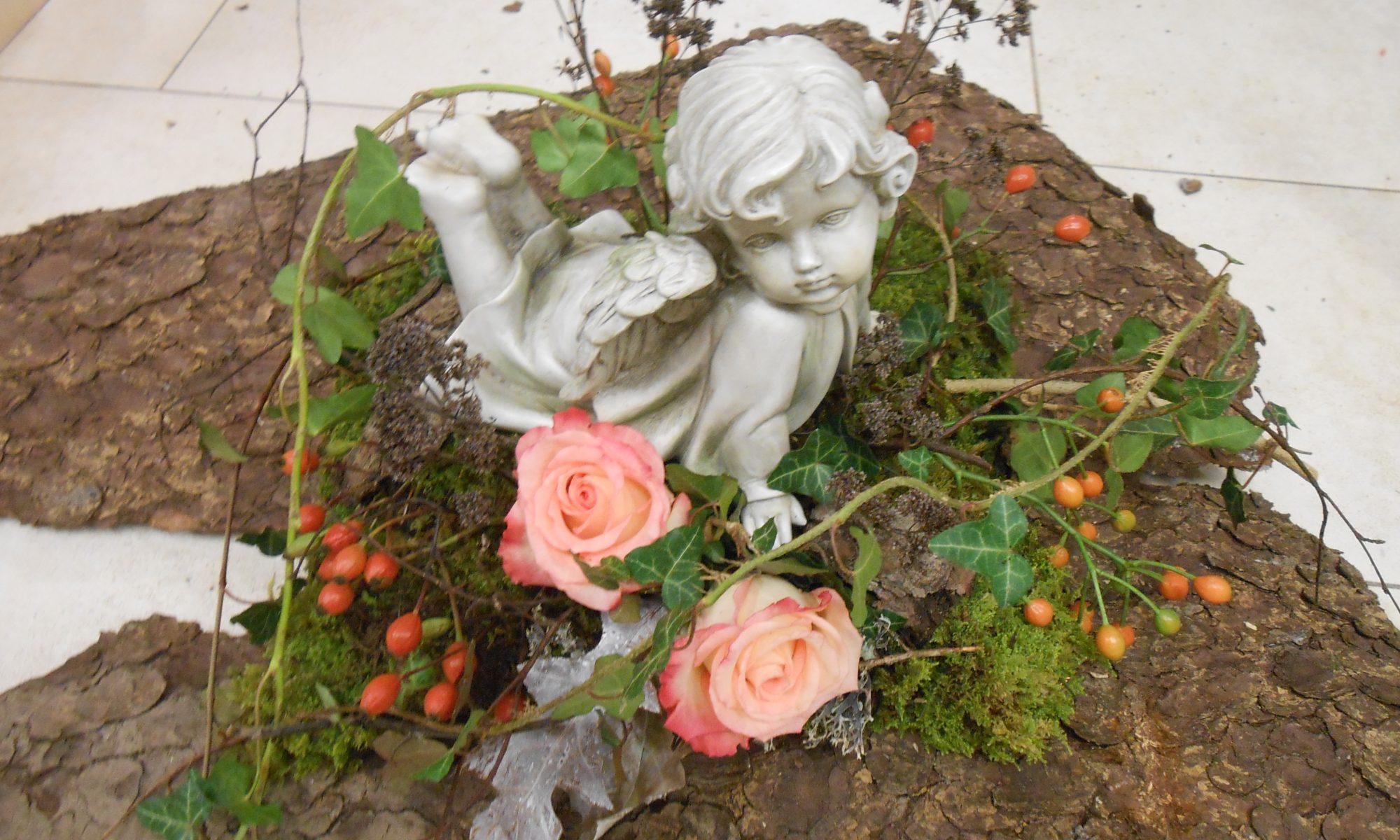 Ein Gesteck auf einer Baumrind bestehend aus zwei rosa Rosen, Hagebutten, Moos, getrockneten Ästen und Efeuranken. In der Mitte vom Gesteck befindet sich ein am Bauch liegender Engel .